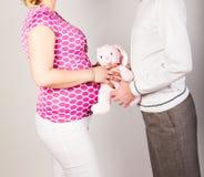 有丈夫和玩具的孕妇 图库摄影