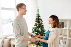 有丈夫的怀孕的妻子在家圣诞节的 免版税库存照片