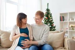 有丈夫的怀孕的妻子在家圣诞节的 免版税库存图片