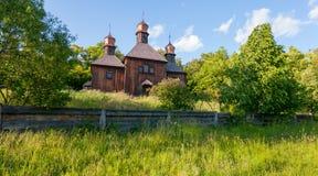 有三个光亮的圆顶的一个老木教会长满与高草 在影片Viy 免版税库存图片