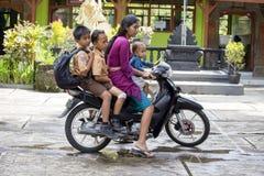 有三个孩子的家庭摩托车、母亲和她的孩子的 运输在亚洲 Ubud,海岛巴厘岛,印度尼西亚 免版税库存照片