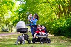 有三个孩子的母亲儿童车和婴儿推车的 库存照片