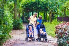有三个孩子的母亲在公园 免版税图库摄影