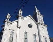 有三个尖顶和深蓝天空的白色新英格兰教会 图库摄影