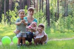 有三个微笑的孩子的愉快的年轻母亲 库存图片