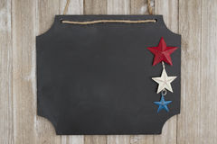 有三个星的垂悬的黑板在被风化的木墙壁上 免版税库存照片