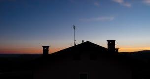有三个烟囱的屋顶在黎明 免版税库存照片