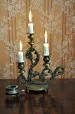 有三个熔化的蜡烛的古色古香的大烛台在一老wallpape 库存照片