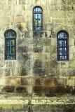 有三个窗口的老教会墙壁 库存图片