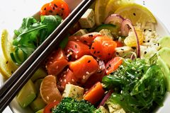 有三文鱼、鲕梨、黄瓜、芝麻菜、硬花甘蓝、米、红萝卜和甜葱的用chuka沙拉,筷子捅碗 免版税库存照片