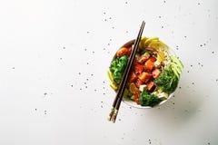 有三文鱼、鲕梨、黄瓜、芝麻菜、硬花甘蓝、米、红萝卜和甜葱的用chuka沙拉,筷子捅碗 库存图片