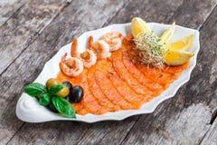 有三文鱼切片和虾的海鲜盛肉盘,装饰用橄榄和柠檬在木背景关闭 库存照片
