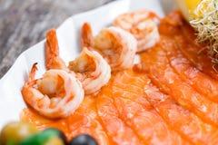 有三文鱼切片和虾的海鲜盛肉盘,装饰用橄榄和柠檬在木背景关闭 免版税库存照片