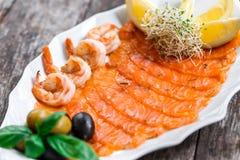有三文鱼切片和虾的海鲜盛肉盘,装饰用橄榄和柠檬在木背景关闭 库存图片