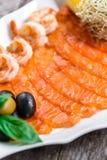 有三文鱼切片和虾的海鲜盛肉盘,装饰用橄榄和柠檬在木背景关闭 免版税库存图片