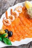 有三文鱼切片和虾的海鲜盛肉盘,装饰用橄榄和柠檬在木背景 图库摄影