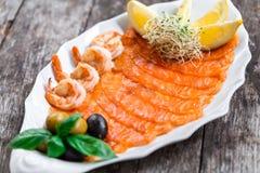 有三文鱼切片和虾的海鲜盛肉盘,装饰用橄榄和柠檬在木背景 免版税图库摄影