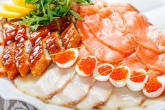 有三文鱼切片的,烟鲟鱼,鹌鹑蛋海鲜盛肉盘用红色鱼子酱,切在木背景的鱼片 库存图片