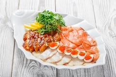 有三文鱼切片的,烟鲟鱼,鹌鹑蛋海鲜盛肉盘用红色鱼子酱,切在木背景的鱼片 免版税库存图片