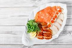 有三文鱼切片的,烟鲟鱼,鹌鹑蛋海鲜盛肉盘用红色鱼子酱,切有芝麻菜的鱼片在木背景 库存图片
