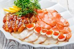 有三文鱼切片的,烟鲟鱼,鹌鹑蛋海鲜盛肉盘用红色鱼子酱,切有芝麻菜的鱼片在木背景 免版税图库摄影