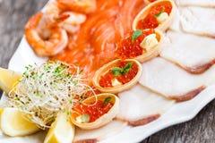 有三文鱼切片的, pangasius鱼,红色鱼子酱,虾海鲜盛肉盘,装饰用橄榄和柠檬在木背景 免版税库存图片