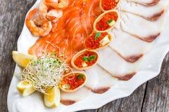 有三文鱼切片的, pangasius鱼,红色鱼子酱,虾海鲜盛肉盘,装饰用橄榄和柠檬在木背景 图库摄影