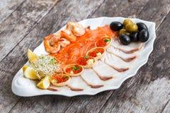 有三文鱼切片的, pangasius鱼,红色鱼子酱,虾海鲜盛肉盘,装饰用橄榄和柠檬在木背景 库存图片