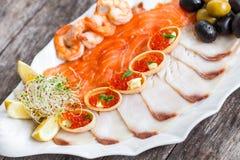 有三文鱼切片的, pangasius鱼,红色鱼子酱,虾海鲜盛肉盘,装饰用橄榄和柠檬 免版税库存图片