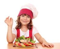 有三文鱼的小女孩厨师 库存图片