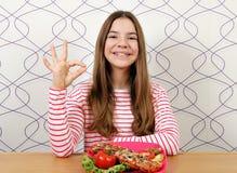 有三明治和ok手标志的十几岁的女孩 图库摄影