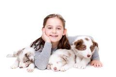 有三条博德牧羊犬小狗的小女孩 免版税图库摄影