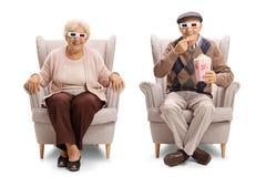 有三维坐在扶手椅子的玻璃和玉米花的前辈 免版税库存图片