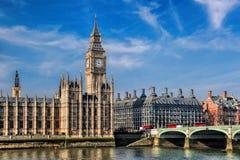 有三辆双层公共汽车的大本钟在桥梁在伦敦,英国 库存照片