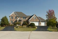 有三辆汽车停车库的大房子 免版税库存图片