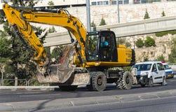 有上升的景气建造场所的黄色挖掘机机器 库存图片