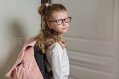 有上学的金发的逗人喜爱的小辈女小学生,站立 免版税库存照片