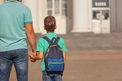 有上有他的父亲的学的背包的逗人喜爱的小男孩 回到视图 免版税图库摄影