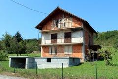 有上的窗口的高未完成的被放弃的红砖家庭郊区与树和清楚的天空蔚蓝的房子和门 库存图片