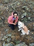 有上釉的杯子的微笑的愉快的女孩用茶在手上和在石岸的聪明的美丽的狗日本人秋田inu 免版税库存照片
