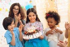 有下垂链子的小俏丽的女孩在她的顶头举行结块与蜡烛在生日的庆祝 免版税库存照片
