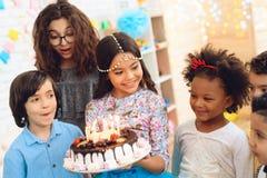 有下垂链子的小俏丽的女孩在她的顶头举行结块与蜡烛在生日的庆祝 免版税图库摄影