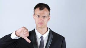有下来拇指的失望的年轻商人 免版税库存照片