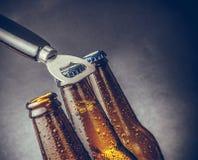 有下落的三个新鲜的冰镇啤酒强麦酒瓶和停止者打开与瓶盖启子 库存图片