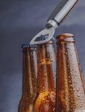 有下落的人开放新鲜的冰镇啤酒强麦酒瓶和停止者打开与瓶盖启子 免版税库存图片