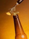 有下落的人开放新鲜的冰镇啤酒强麦酒瓶和停止者打开与瓶盖启子 图库摄影