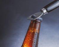 有下落的新鲜的冰镇啤酒强麦酒瓶和停止者开放与瓶盖启子 免版税库存图片
