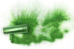 有不可思议溢出的绿色的闪烁的,溢出在瓶子外面的神圣绿色闪烁瓶子隔绝在白色背景 免版税库存照片