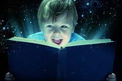 有不可思议的书的笑的小男孩 库存图片