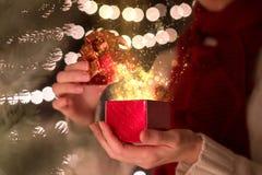 有不可思议的光光芒的妇女开放圣诞节礼物盒  免版税库存图片